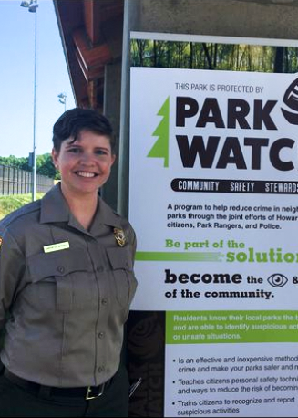 Amy Carpenter Driscoll stand in front of a sign for Park Watch a program she started