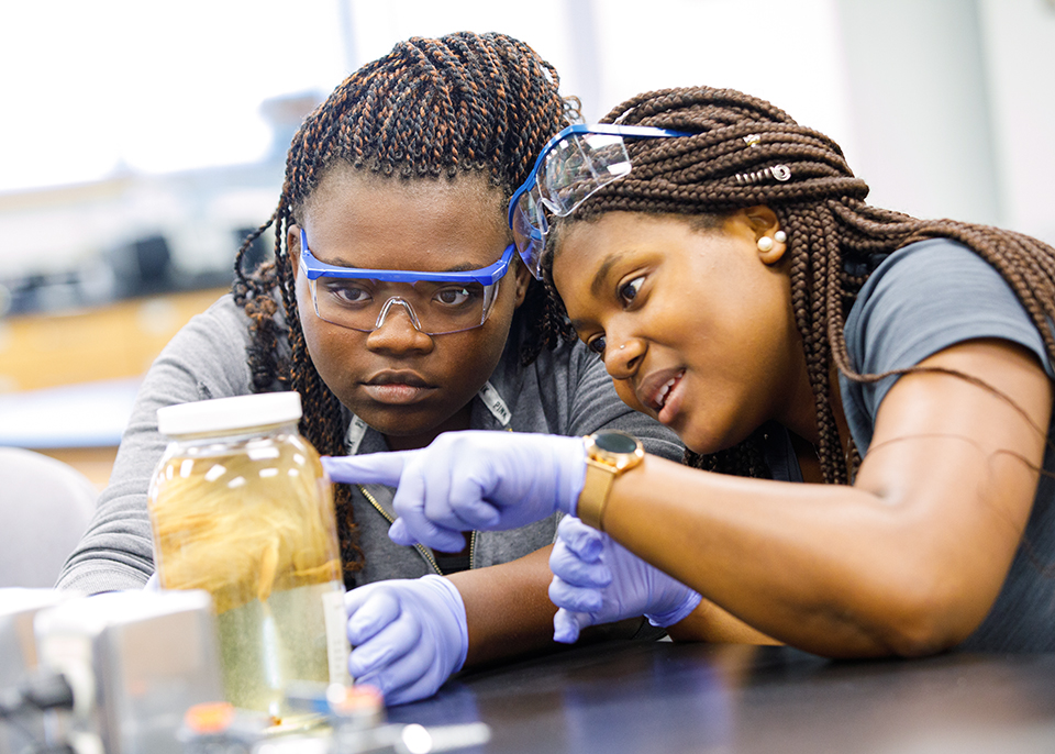 2 female students observe jar in lab class