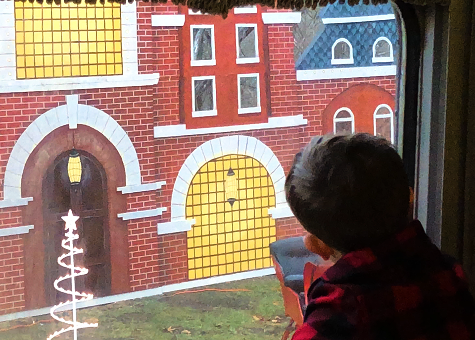 "boy looks out window of train to see ""Santa's North Pole castle"""