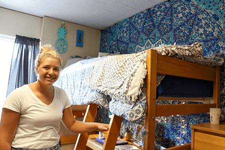 Girl standing next to her bunk